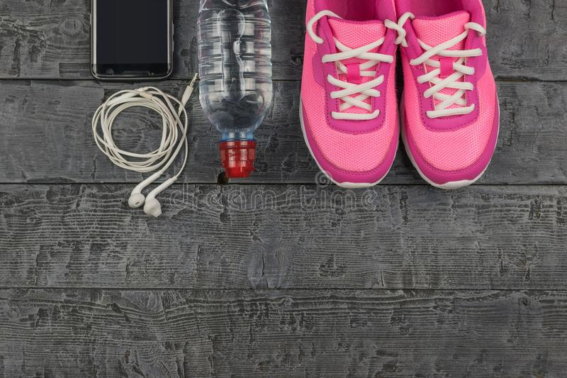Beautiful pink sneakers, headphones, water and apples on a wooden dark floor. View from above. Pink running shoes for fitness classes at the gym and a ripe royalty free stock photos