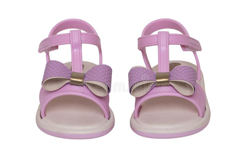 Pink sandals isolated. Close-up of cute pink sandals with a bow for the little girl isolated on a white background. Trendy summer royalty free stock images