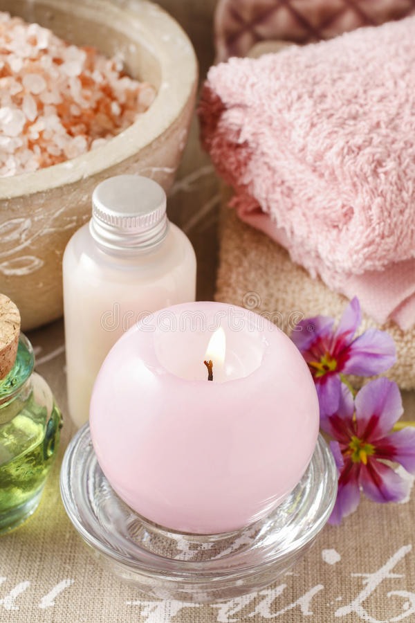 Pink scented candle, soft towels and bowl of sea salt. Spa time royalty free stock photo
