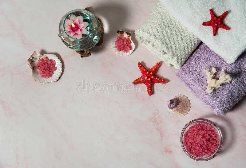 Pink sea salt crystals, towels, burning floating candles, starfish, shells and corals on a pink marble background. royalty free stock photos