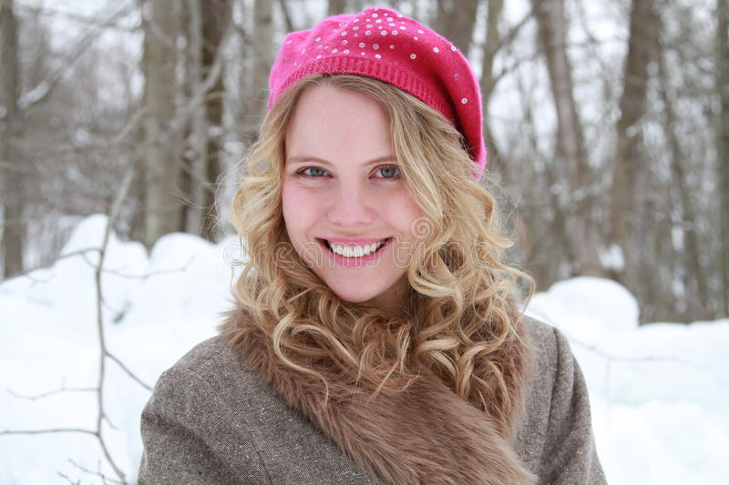 Pink Sequined Beret and Fur Jacket Coy Happy Woman. Portrait of a happy, smiling, wholesome, beautiful young woman wearing a fur jacket and pink beret in a snowy royalty free stock photos