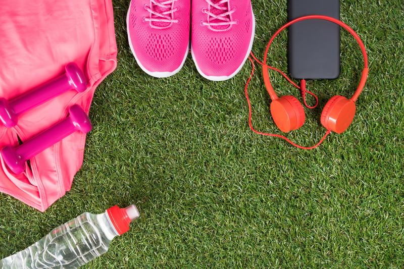 Pink set of sports things for fitness with music and a bottle of water on a green lawn. Pink set of sports things for fitness with music and a bottle of water on stock photos