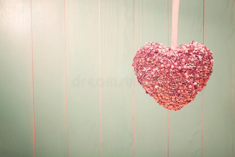 Pink shiny heart on vintage green wood background stock photo