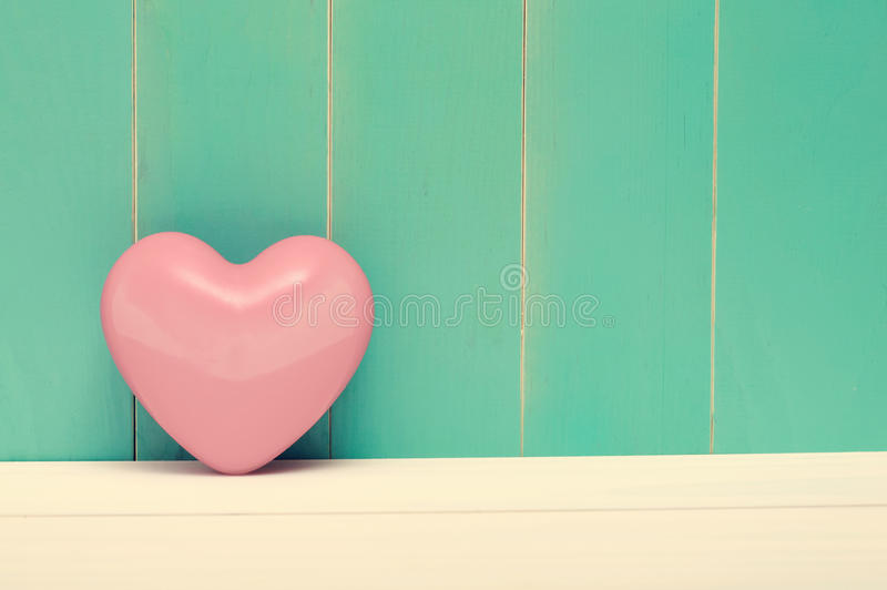 Pink shiny heart on vintage teal wood royalty free stock photo