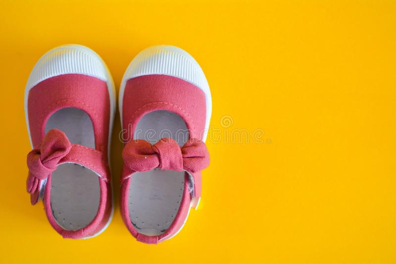 Pink shoes for children isolated. On a yellow background royalty free stock photography