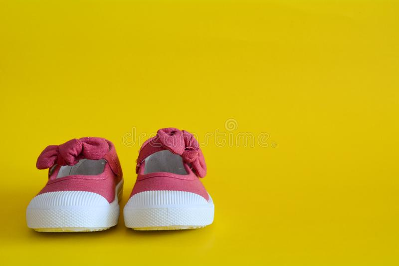 Pink shoes for children isolated. On a yellow background royalty free stock photos