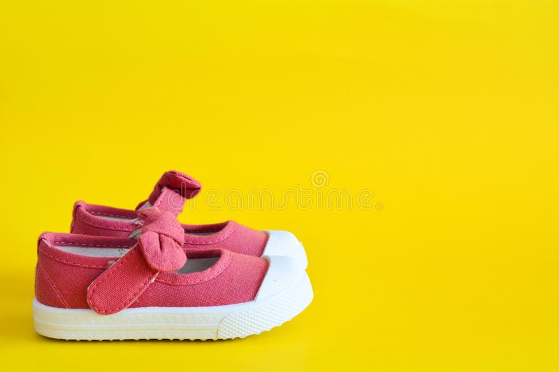 Pink shoes for children isolated. On a yellow background stock photography