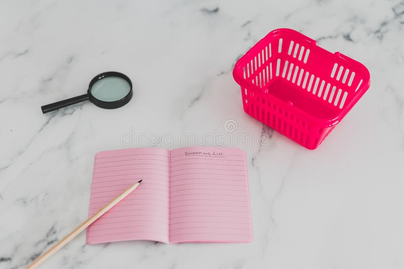 Pink shopping basket on marble desk with magnifying glass and list on notebook. Pink shopping basket on marble desk with magnifying glass, concept of analyzing stock photos