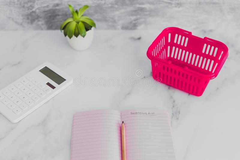 Pink shopping basket on marble desk with shopping list notebook magnifying glass and calculator. Concept of analyzing your expenses and budgeting stock image