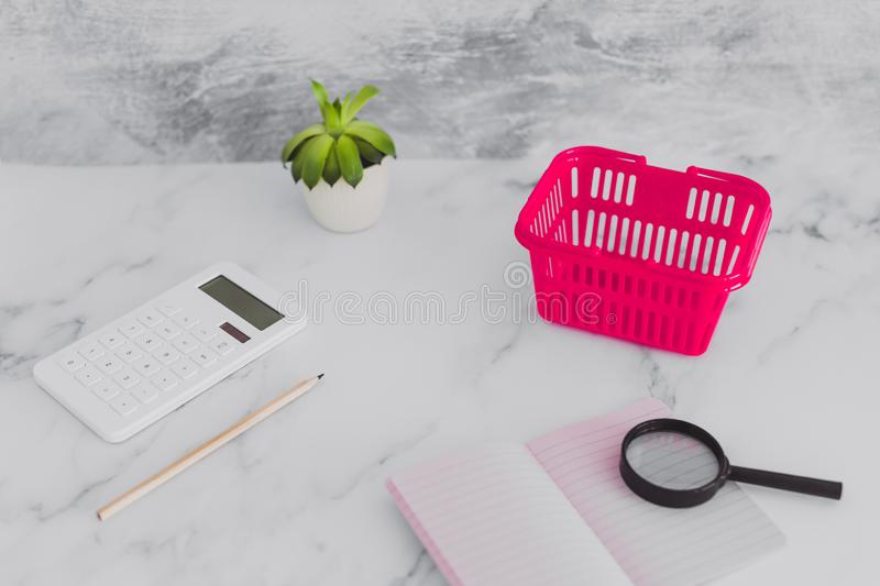 Pink shopping basket on marble desk with shopping list notebook magnifying glass and calculator. Concept of analyzing your expenses and budgeting stock photography