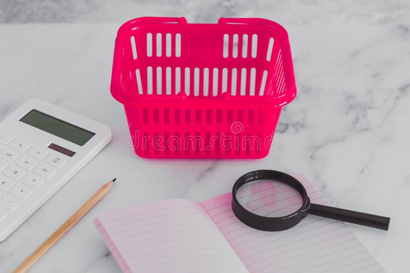 Pink shopping basket on marble desk with shopping list notebook magnifying glass and calculator. Concept of analyzing your expenses and budgeting royalty free stock photography
