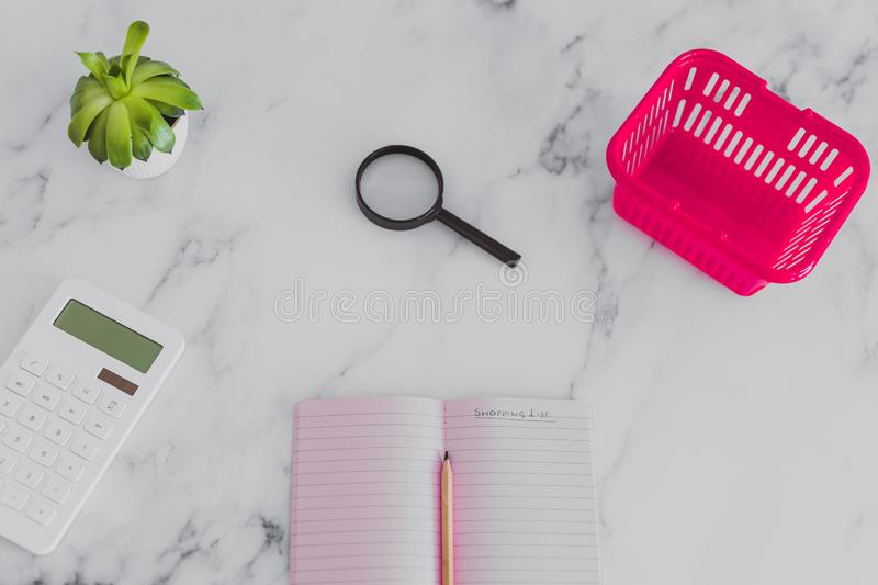 Pink shopping basket on marble desk with shopping list notebook magnifying glass and calculator. Concept of analyzing your expenses and budgeting stock photos