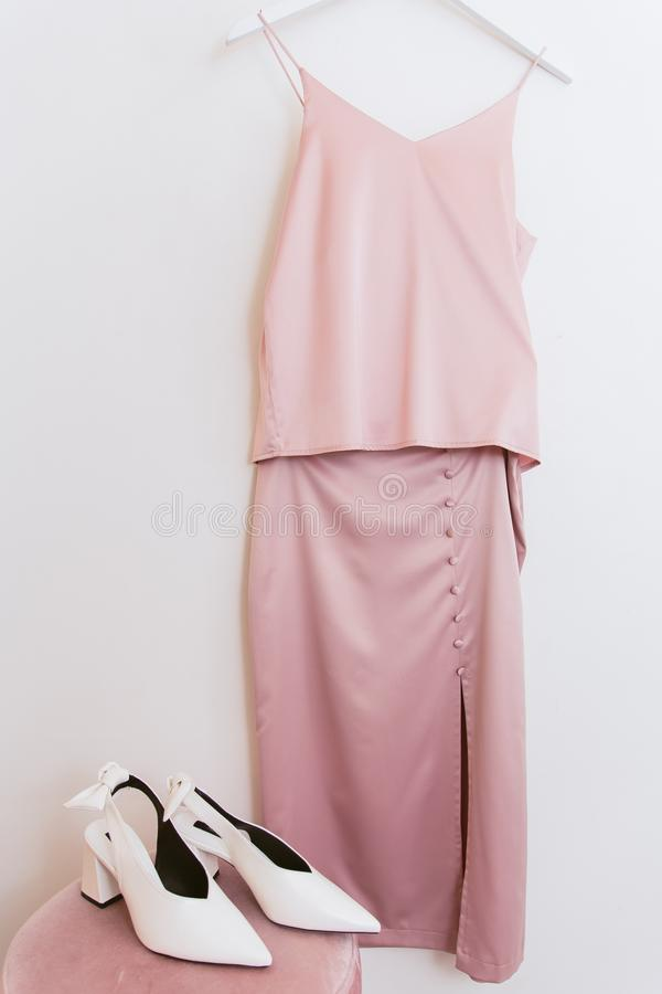Pink silk blouse and skirt on a hanger in the dressing room and white shoes on the pouf. Clothes and clothes in the locker room in. The store on the hanger royalty free stock images