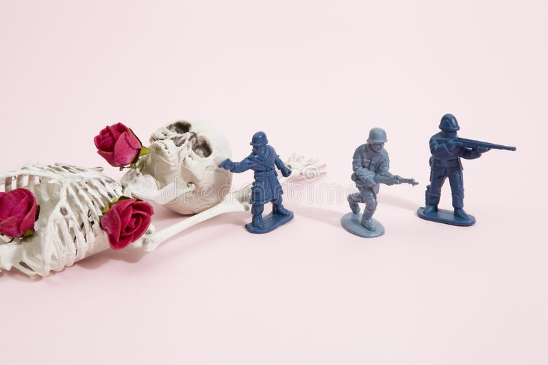 Pink skeleton and soldiers. Plastic toy Soldiers around a pop skeleton wearing flower roses on a pop vibrant pink background. Minimal color still life stock photo
