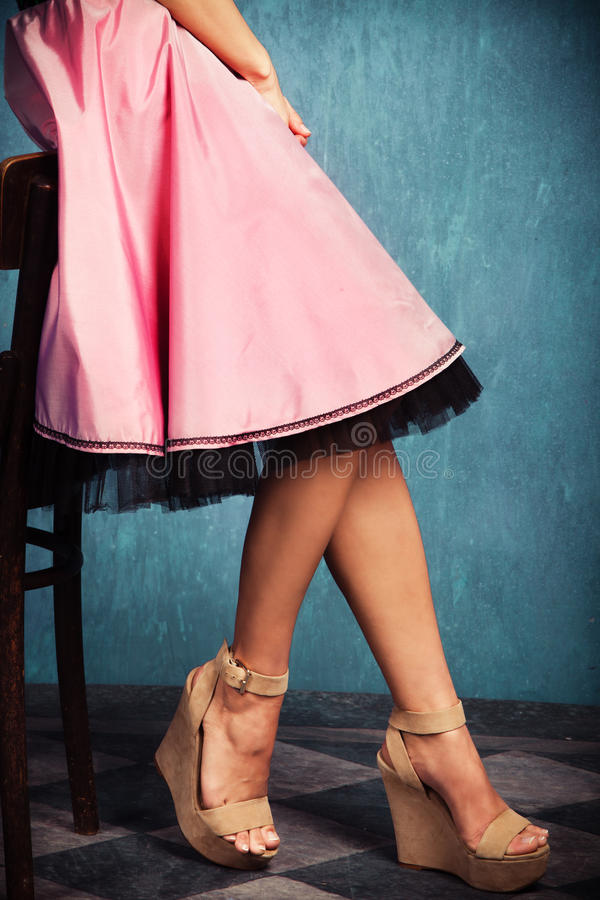 Pink skirt and wedge high heel shoes. Female legs in wedge high heel shoes and romantic pink skirt royalty free stock images