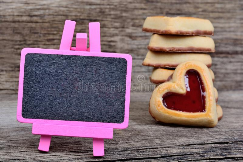 Pink small blackboard with heart cookies on table royalty free stock images
