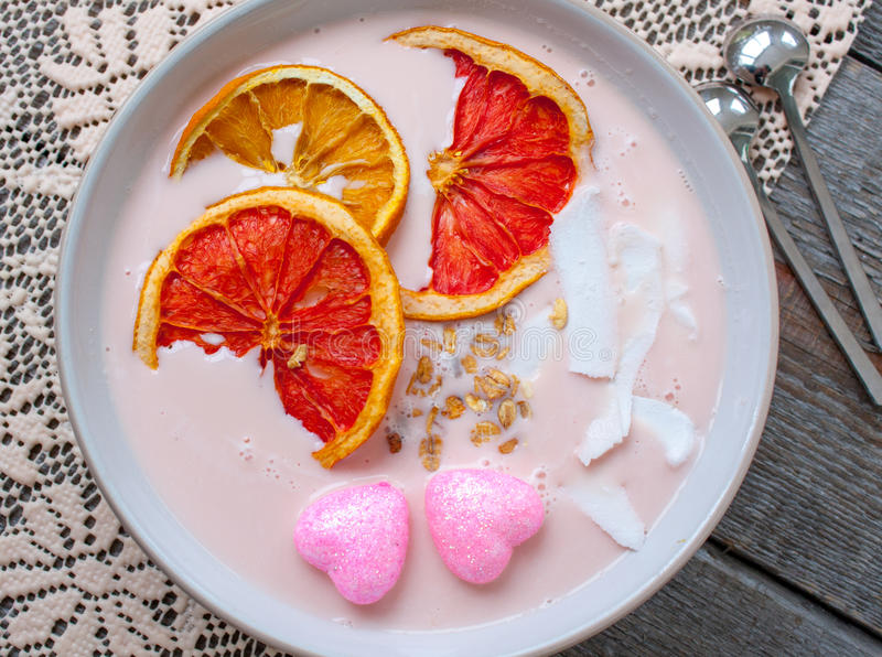 Pink smoothies with raspberry. Coconut, oranges and granola. Breakfast on Valentine`s Day stock image