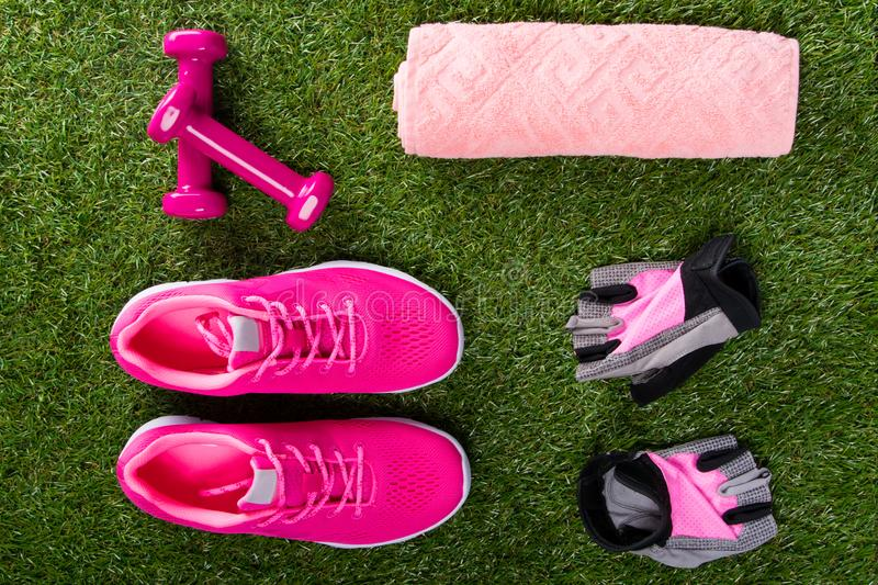 Pink sneakers and gloves, dumbbells for fitness, towel, on the background of grass. Pink sneakers and gloves, dumbbells for fitness, towel, on the background stock photography