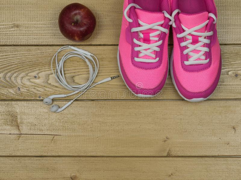 Pink sneakers and a red Apple on a wooden floor. The view from the top. Pink running shoes for fitness classes at the gym and a ripe Apple on a wooden floor royalty free stock images