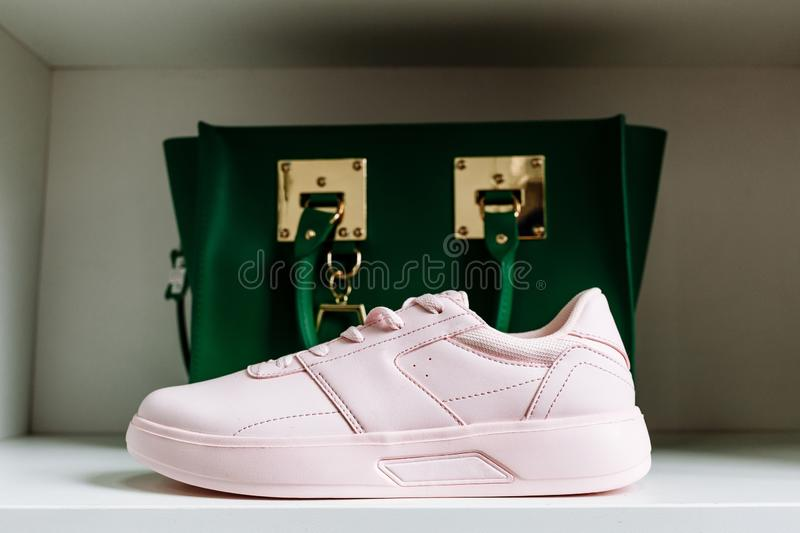 Pink sneakers with thick soles and a green bag in the background on the white shelf of the store stock images