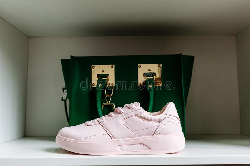 Pink sneakers with thick soles and a green bag in the background on the white shelf of the store royalty free stock photos