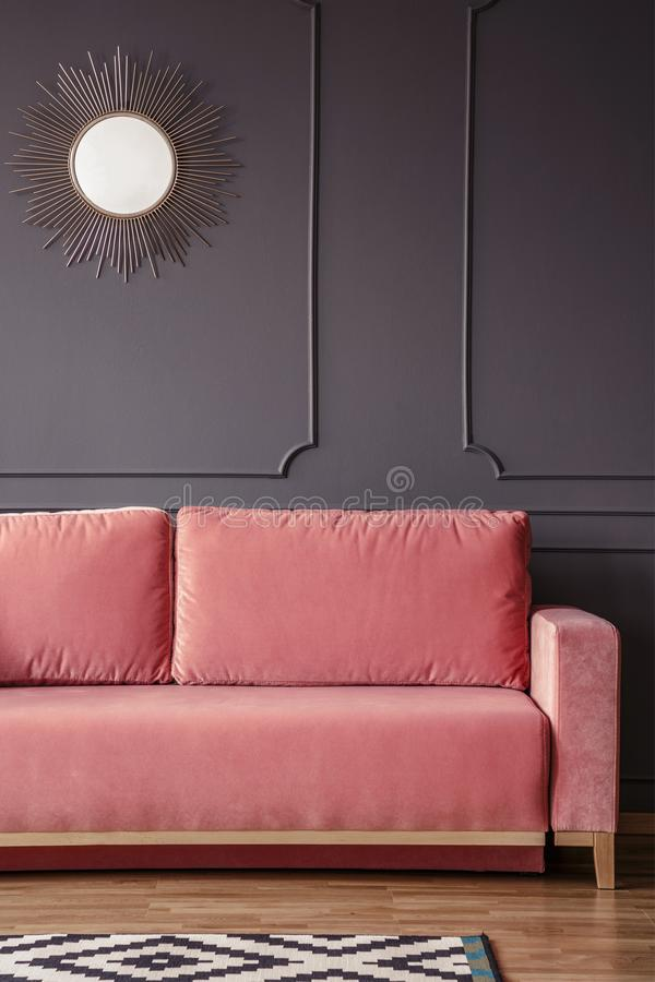 Pink sofa against grey wall with round gold mirror in dark living room interior. Real photo royalty free stock image