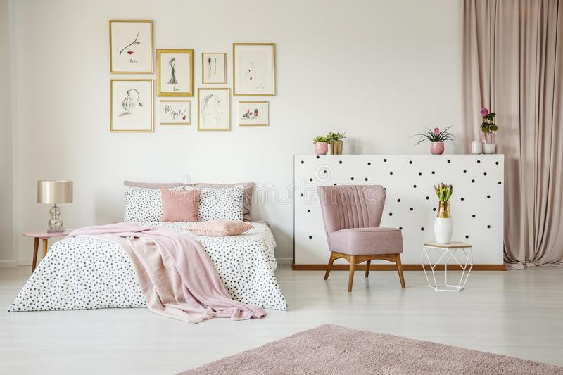 Pink spacious bedroom interior. Pink armchair in spacious bedroom interior with blanket on bed against white wall with posters stock images