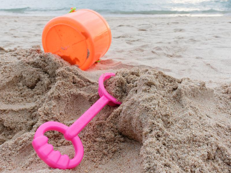 Pink spade and orange plastic bucket of sand tool toy set for kid and toddler on the sand over beach background. Pink spade and orange plastic bucket of sand royalty free stock photo
