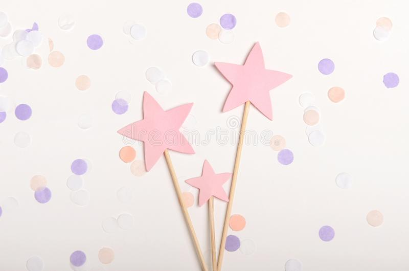 Pink stars on a stick topping on white background with confetti, pastel colors. Children`s holiday, new year. Top view. Flat lay royalty free stock photo