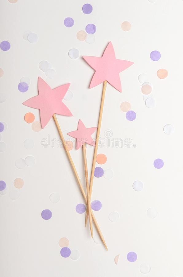 Pink stars on a stick topping on white background with confetti, pastel colors. Children`s holiday, new year. Top view. Pink stars on a stick topping on a white royalty free stock photo