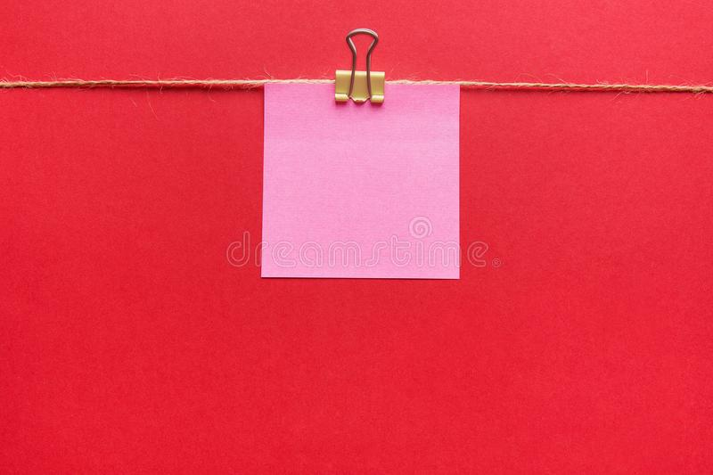 Pink sticky note hanging on paper clip on twine on dark red background. Announcement message memo mockup. Business ideas concepts. Projects time planning royalty free stock photos