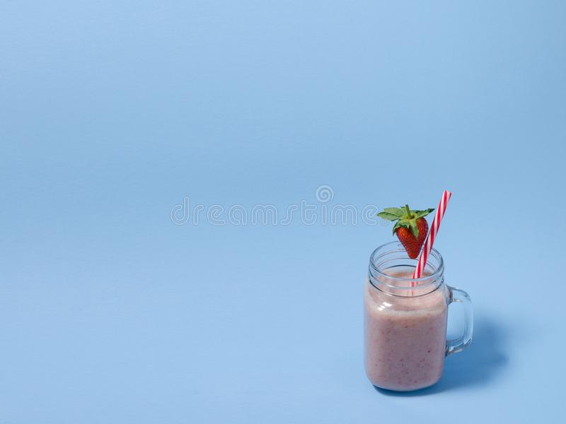 Pink strawberry smoothie in a mason jar glass with straw and scattered berries on blue background. Healthy and delicious breakfast. Organic Strawberry Smoothie stock images