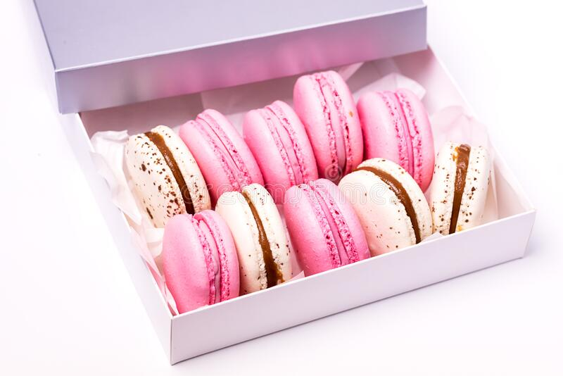 Pink Strawberry and White Caramel and Salt Macarons in Box French Delicate Dessert Pink and White Pastel Macarons.  royalty free stock photo