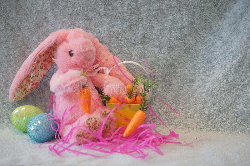 Pink stuffed bunny rabbit with his basket of carrots. royalty free stock photos