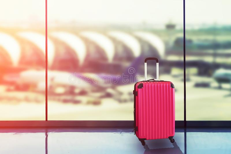 Pink suitcases in airport departure lounge, airplane in background. Summer vacation concept, traveler suitcases in airport terminal waiting area stock photo