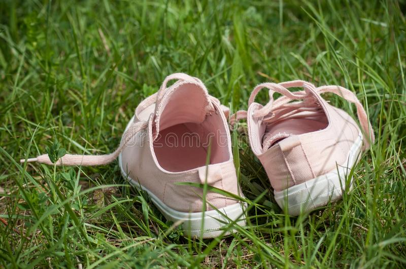 Pink summer sneakers in the grass. Closeup of pink summer sneakers in the grass royalty free stock photo