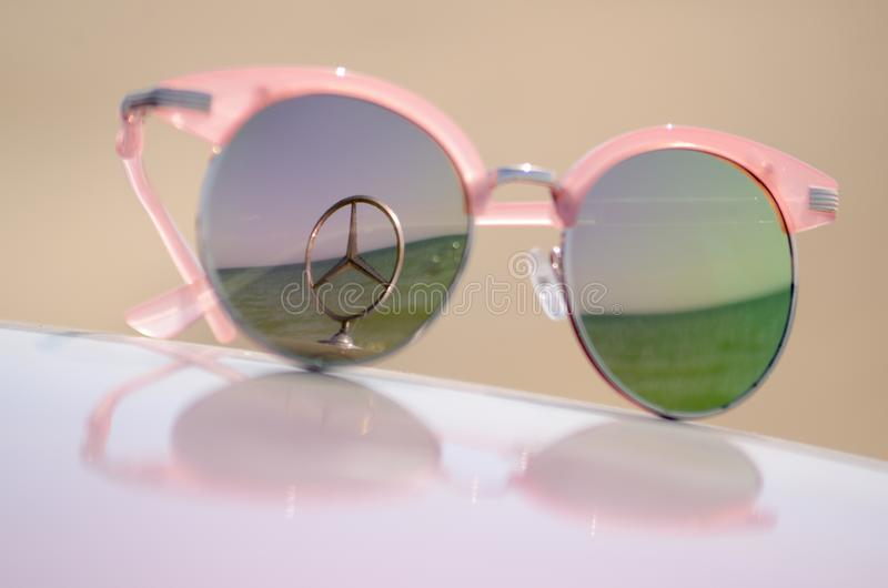Pink sunglasses against the sun on the hood of a car with a star Mercedes emblem stock photos