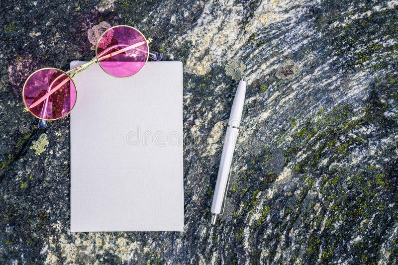 Pink sunglasses and blank paper on mossy stone background stock images