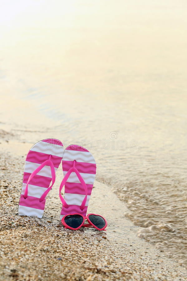 Pink sunglasses. With pair of flip flops on the beach sand stock photos