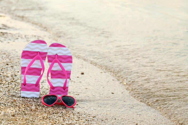 Pink sunglasses. With pair of flip flops on the beach sand royalty free stock photo
