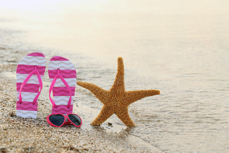 Pink sunglasses. With pair of flip flops and starfish on the beach sand royalty free stock photos