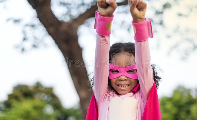 Pink superhero girl at park royalty free stock photo
