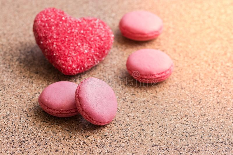 Pink sweet french macaroons and sugar heart. Valentine`s Day. Selective focus stock photography