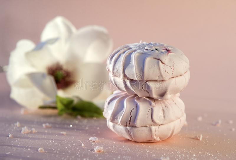Pink sweet marshmallow, Magnolia flower on beige background, dessert, food. Sweets stock photo
