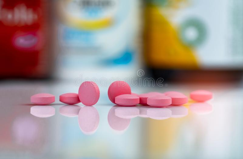 Pink tablets pills on blurred background of drug box and drug bottle. Vitamins and supplements tablets. Pharmacy drugstore. Pharmaceutical products. Healthcare stock photos