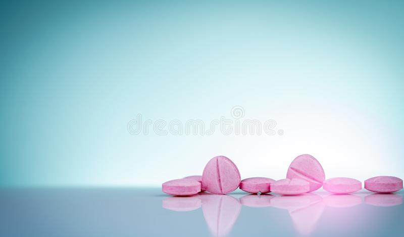 Pink tablets pills with shadow on gradient background. Pharmaceutical industry. Pharmacy products. Vitamins and supplements. Medication use in hospital or stock photography