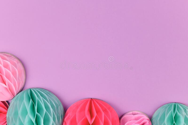 Pink and blue honeycomb shaped paper balls on pastel violet background with blank copy space. Pink and teal blue honeycomb shaped paper balls at bottom of pastel stock photos
