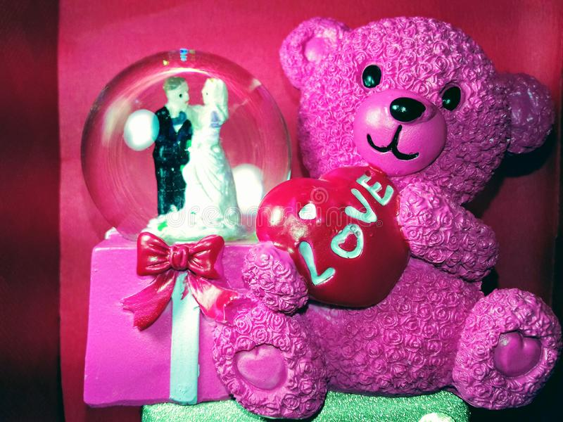 Pink teddy bear with love symbol and red background wallpaper beautiful colours combination royalty free stock photo