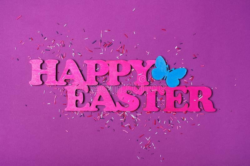 Pink text of happy easter and bright colorful sugar sprinkles or confetti as baking decor. Top view on pink text of happy easter and bright colorful sugar stock images