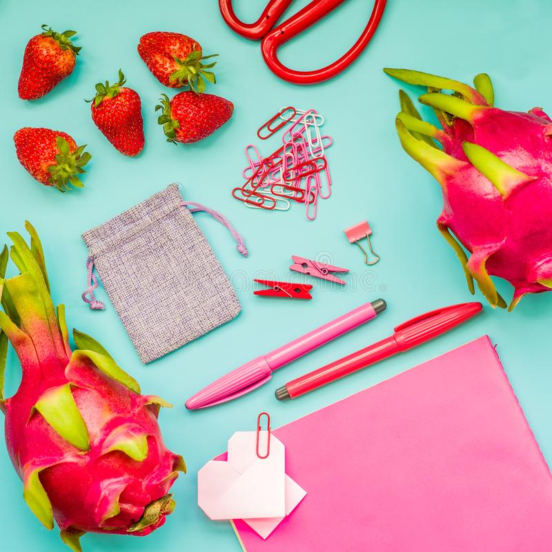 Pink things on blue background. strawberries and dragonfruit with stationary on blue background royalty free stock image